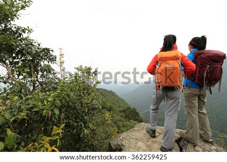 two successful backpacker enjoy the beautiful landscape at mountain peak