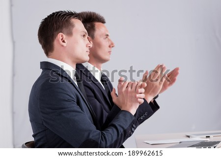 Two successful businessmen clap their hands and have conversation in office.Handsome men are sitting at laptop working on the tablet. Confident businessmen smiling  in formal wear