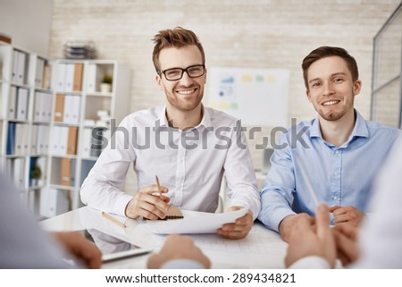 Two successful businessmen looking at camera at workplace in office - stock photo