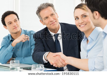 Two Successful Businessmen Shaking Hands In Front Of Their Colleague - stock photo