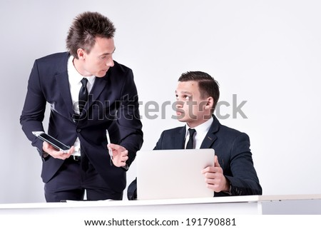 Two successful businessmen sitting at desk and have conversation in office.Handsome men are sitting at laptop working on the tablet. Confident businessmen smiling  in formal wear and writing on paper