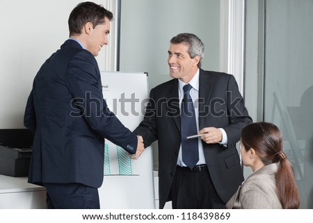 Two successful businesspeople giving handshake in the office - stock photo