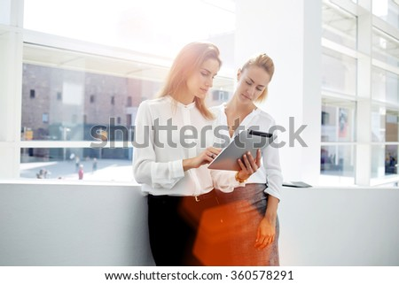 Two successful businesswomen checking list of affairs on digital tablet while standing in office interior, two female partners met in the hallway and stopped for consult new project on touch pad   - stock photo