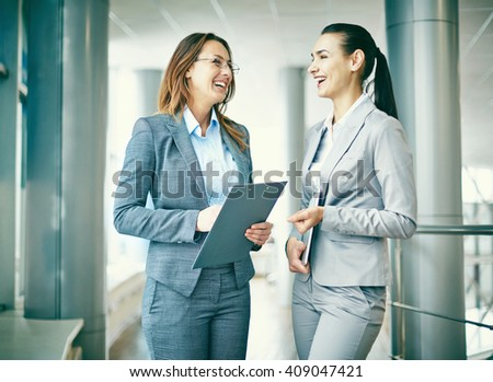 Two successful businesswomen talking and laughing - stock photo