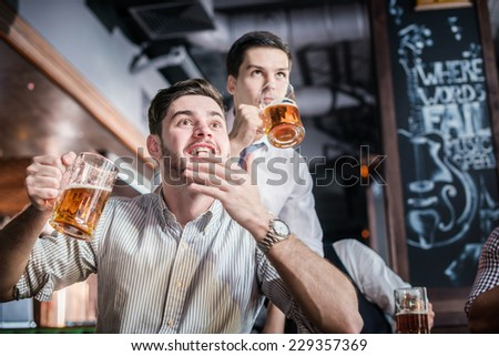 Two successful friends businessmen drink beer and rejoice and shout together watching TV at the bar. Confident business people having fun with friends at the bar with a beer watching football on TV - stock photo