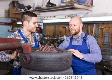 Two successful smiling car mechanics working together at workshop - stock photo