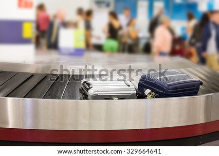 Two suitcases on the luggage belt in the airport hall - stock photo