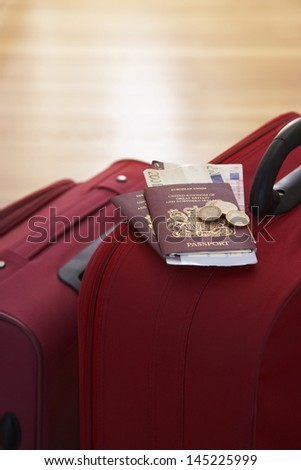 Two suitcases with passports on them standing in hallway elevated view close up - stock photo
