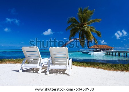 Two sun beds on beautiful beach at Maldives - stock photo