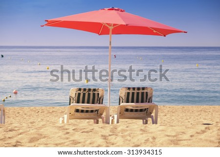 Two sun beds with red umbrella on a tropical beach with a beautiful ocean view - stock photo