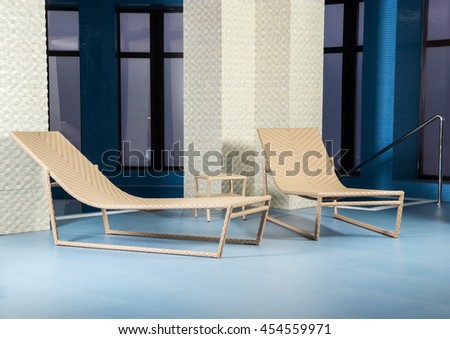 Two sun loungers around pool in room