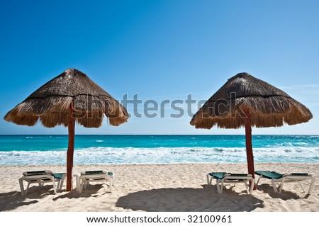 Two sun umbrellas by the beach - stock photo