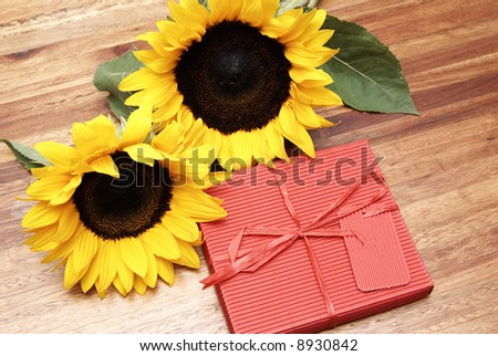 Two sunflowers and a red box on a wooden table - stock photo