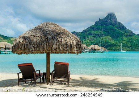 Two sunlounger chairs under a thatched parasol on a sand beach with a view on the lagoon and Mount Otemanu on the tropical island of Bora Bora, near Tahiti, in French Polynesia. - stock photo