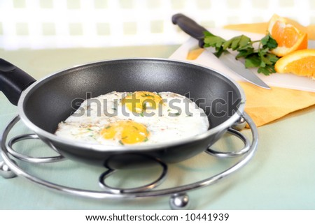 two sunny side up eggs in frying pan with cut up orange on cutting board in the backgroun ready for breakfast - stock photo