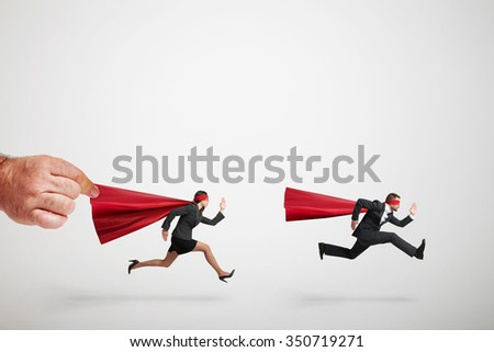 two superheroes fast running but big mans hand holding red cloak of superwoman over light grey background - stock photo