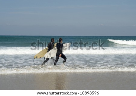 two surfers entering the water