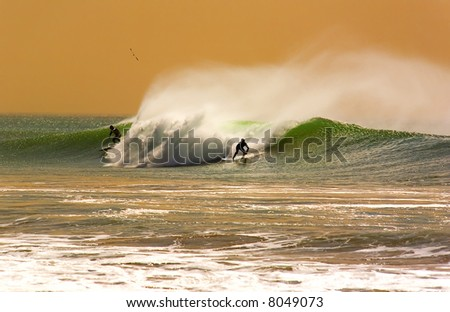 Two Surfers on a wave in a Fantasy shot. - stock photo