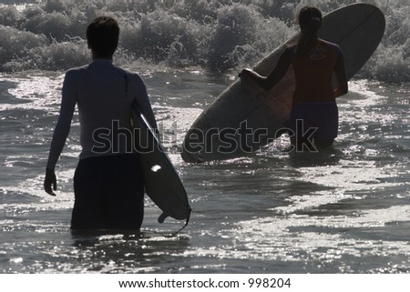 Two surfers, one man, one woman, walking into the ocean.  They are partially silhouetted by the backlighting, water is glistening.