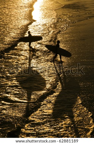 two surfers walking in silhouette on a beach. - stock photo