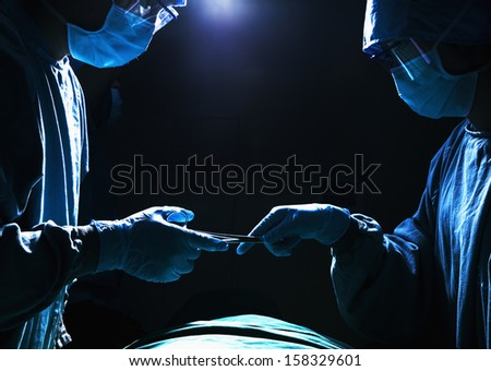 Two surgeons working and passing surgical equipment in the operating room - stock photo