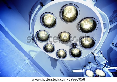 Two surgical lamps in operation room. Blue cast light represent purity and clinical mood. Useful file for your hospital brochure, medical article and other purpose. - stock photo