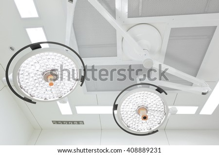 Two surgical lamps in operation room take with selective color technique and art lighting - stock photo