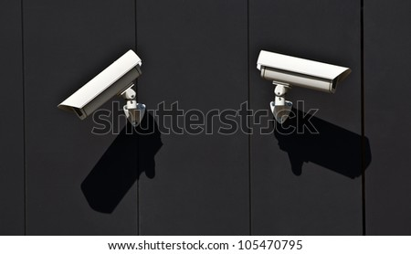 two surveillance cameras on the wall of a public building - stock photo