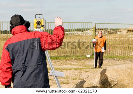 Two surveyor workers with theodolite equipment outdoors - stock photo