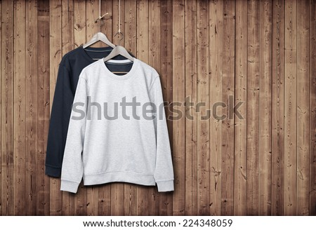 Two sweaters on a dark wood wall