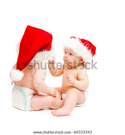 Two sweet Christmas baby friends in diapers and Santa hats, isolated - stock photo