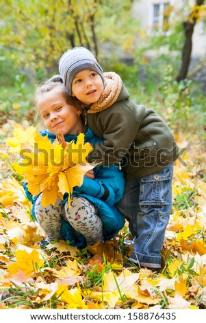 Two sweet kids sitting on the autumn leaves