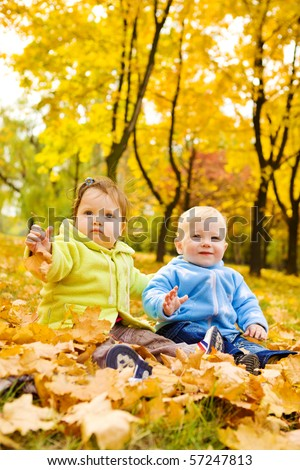 Two sweet kids sitting on the autumn leaves - stock photo