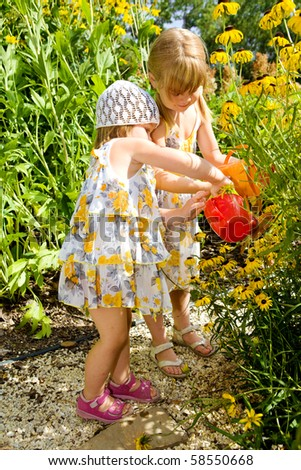 Two sweet kids watering flowers in the garden - stock photo