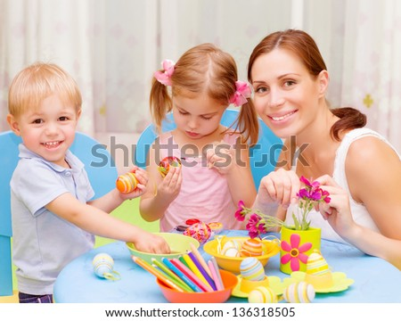 Two sweet toddler with young drawing teacher paint colorful Easter eggs, art lesson, handmade festive decor - stock photo