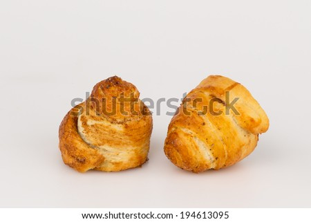 two sweet vanilla sugar cinnamon rolls similar to a spiral on white background
