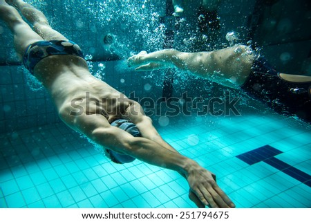 Two swimmers at the swimming pool.Underwater photo. - stock photo