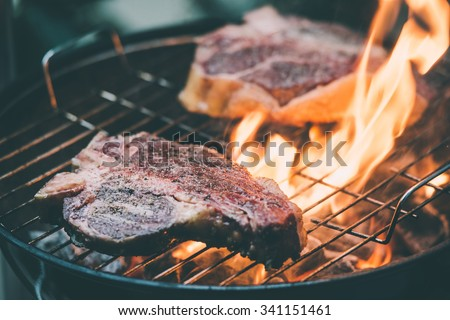 Two t-bone florentine beef steaks on the grill with flames. Toned picture - stock photo
