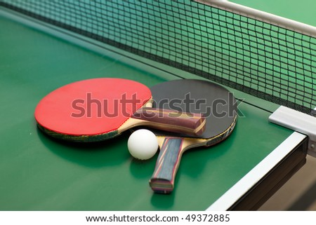 Two table tennis or ping pong rackets and ball on a green table with net; shallow DOF, focus on rackets - stock photo