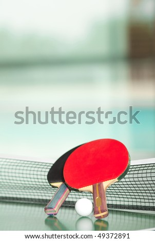 Two table tennis or ping pong rackets and ball on a green table with net, swimming pool in the background; shallow DOF, focus on rackets - stock photo