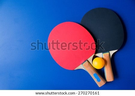 Two table tennis or ping pong rackets and balls on a blue table  - stock photo