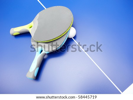 Two table tennis or ping pong rackets and balls on a blue table with net; shallow DOF, focus on rackets - stock photo