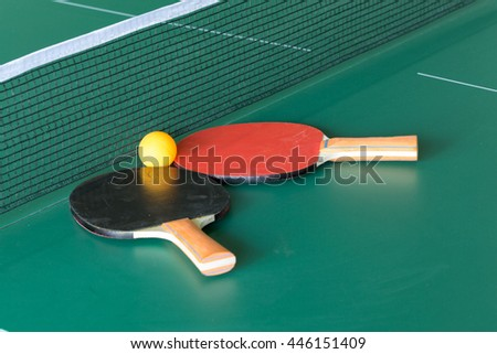 Two table tennis or ping pong rackets and balls on a green table with net - stock photo