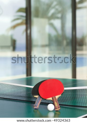 Two table tennis or ping pong rackets and balls on a green table with net, swimmig pool, palm tree and sea in the background; shallow depth of field, selective focus on rackets. - stock photo