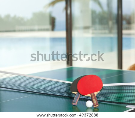 Two table tennis or ping pong rackets and balls on a green table with net,  swimming pool and sea in the background; shallow DOF, focus on rackets - stock photo