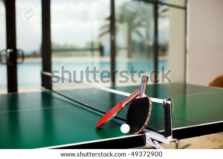 Two table tennis or ping pong rackets and balls on a green table with net, swimming pool, palm tree and sea in the background; shallow DOF, focus on rackets - stock photo