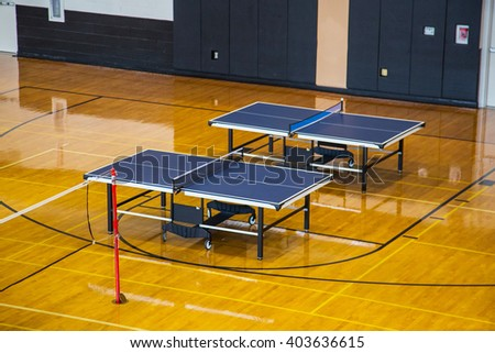 Two table tennis tables standing in the gym of university - stock photo