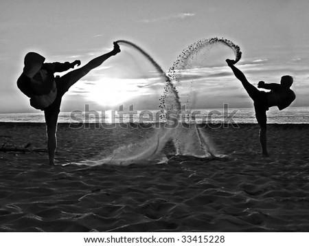 Two taekwondo fighters kicking on the beach - stock photo