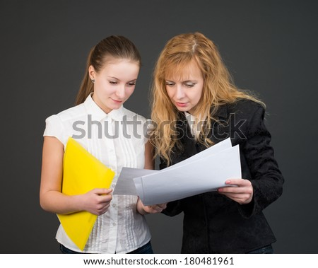 Two talking businesswomen with documents. - stock photo