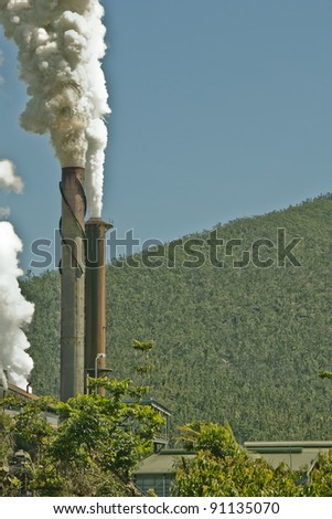 two tall chimney stacks blowing out smoke
